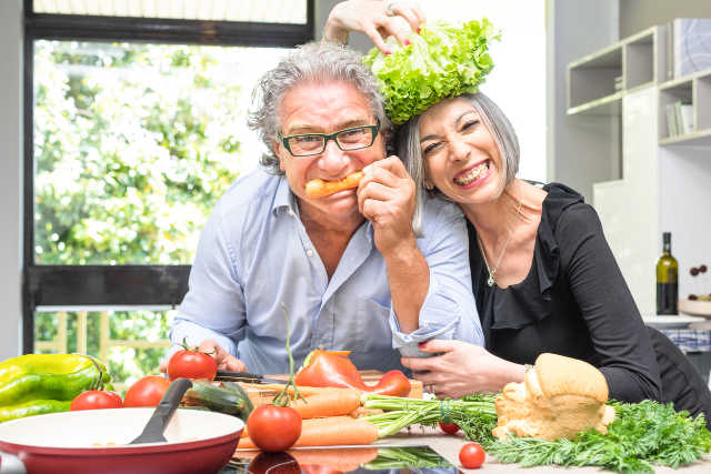 Ehepaar beim Kochen, scherzend mit Gemüse