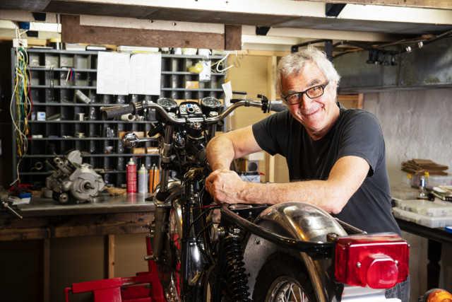 Älterer Mann in einer Werkstatt mit einem alten Motorrad