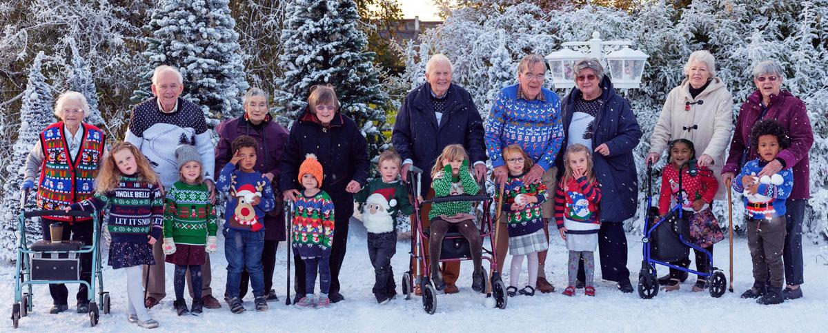 Die beschriebene Seniorengruppe mit gleich vielen kleinen Kundern in einer verschneiten WInterlandschaft