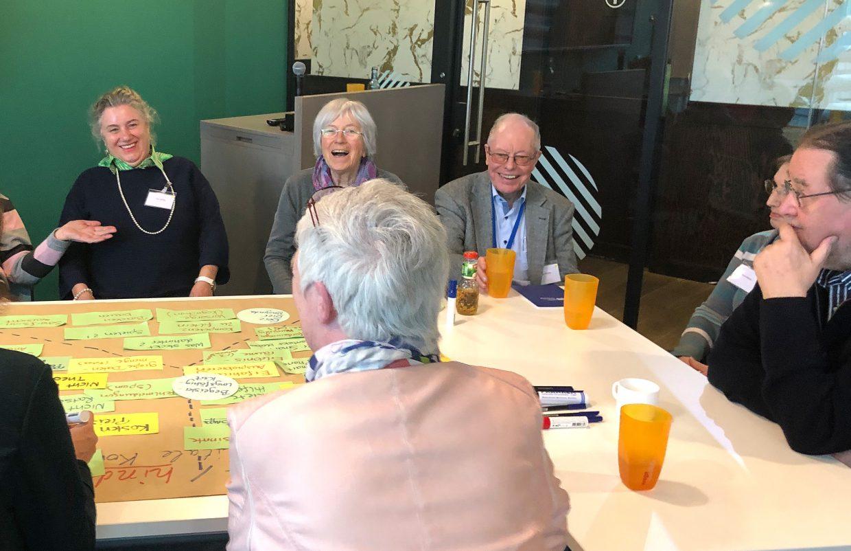 Lachende ältere Menschen um einen Tisch