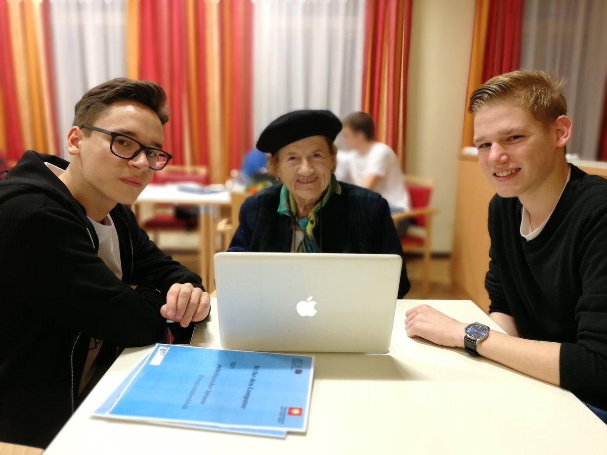 Eine ältere Dame mit zwei jungen Schülern vor einem Laptop