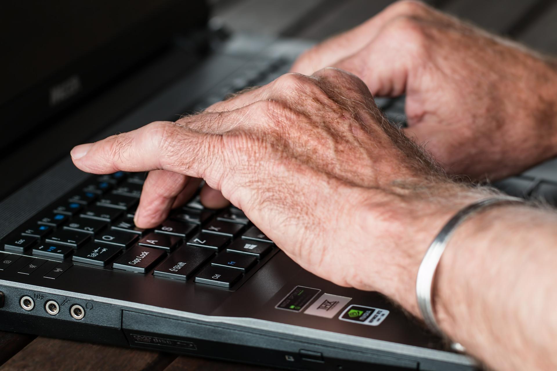 Hände eines älteren Menschen auf einer Computertastatur